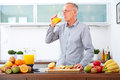 Mature man drinking orange juice in the kitchen ii freshly squeezed Royalty Free Stock Images