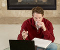 Mature man drinking water while working on assignments at home photo of sitting down glass table from looking computer screen with Stock Images