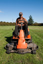 Mature man driving grass cutter Stock Photography