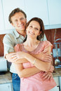 Mature man embracing a pretty woman in the kitchen Stock Images