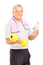 A mature man exercising with a dumbbell and holding a bottle  Stock Photos