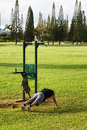Mature man exercising outdoors doing pushups on the grass at an exercise park fitness concepts Royalty Free Stock Photography