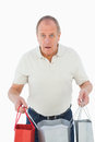 Mature man feeling buyers remorse holding bags on white background Stock Images