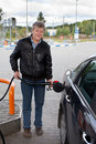 Mature man filling car with gasoline in Royalty Free Stock Images