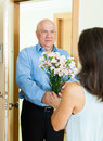 Mature man giving bunch of flowers to woman men women at home door Stock Photo