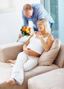 Mature man giving flowers to his pregnant wife Royalty Free Stock Images
