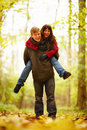 Mature man giving woman a piggy back in forest Royalty Free Stock Photo