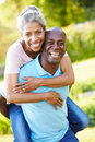Mature man giving woman piggyback in countryside smiling at camera Royalty Free Stock Photography
