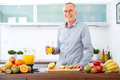 Mature man with a glass of orange Juice in the kitchen, smiling Royalty Free Stock Photo