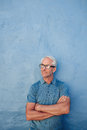 Mature man with glasses looking away at copy space portrait of a standing his arms crossed against a blue wall caucasian male Stock Image