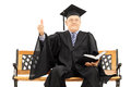 Mature man in graduation gown on bench giving a thumb up seated wooden holding book and isolated white background Stock Image