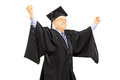 Mature man in graduation gown gesturing success with hands isolated on white background Stock Images