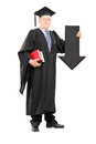 Mature man in graduation gown holding big arrow pointing down full length portrait of a black isolated on white background Royalty Free Stock Photo