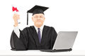 Mature man in graduation gown posing with diploma and laptop on Royalty Free Stock Photos
