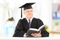 Mature man in graduation gown reading book seated on table Stock Photography