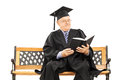 Mature man in graduation gown seated on bench reading book a isolated white background Stock Photos