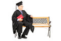 Mature man in graduation gown sitting on wooden bench Stock Photography