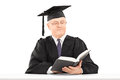 Mature man with graduation hat reading book seated on table a isolated white background Stock Images