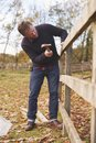 Mature Man Hammering Nail Into Repaired Fence Royalty Free Stock Photo