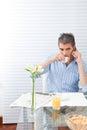 Mature man having breakfast using phone Stock Photo