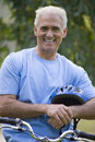 Mature man with helmet on bicycle smiling portrait Stock Photography