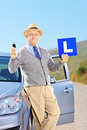 Mature man on his car holding a l sign and key after having his smiling driver s licence outside Stock Photography