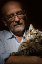 Mature man with his cat low key shot of Royalty Free Stock Photos
