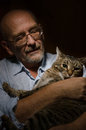 Mature man with his cat low key shot of Stock Photography