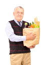 Mature man holding a bag full of groceries isolated on white background Royalty Free Stock Photo