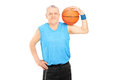Mature man holding a basketball over his shoulder isolated on white background Stock Images