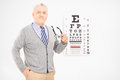 Mature man holding a pair of glasses in front of an eye chart eyesight test Royalty Free Stock Photo