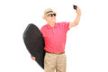 Mature man holding a surfboard and taking selfie isolated on white background Royalty Free Stock Images