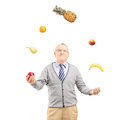 A mature man juggling fruits isolated on white background Royalty Free Stock Image