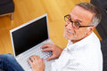 Mature man with laptop and reading specs looking to camera Royalty Free Stock Photo