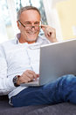 Mature man with laptop and reading specs senior Stock Photography