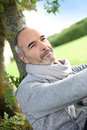 Mature man leaning on tree in countryside senior sitting park and enjoying quietness Royalty Free Stock Photo