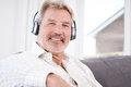 Mature Man Listening To Music On Wireless Headphones Royalty Free Stock Photo