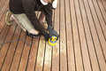 Mature man performing maintenance on home wooden deck Royalty Free Stock Photo