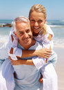 Mature man piggybacking his wife at the beach Stock Image