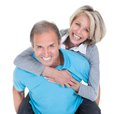 Mature man piggybacking his wife happy over white background Stock Photo
