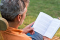 Mature man reading book close up of sitting on lounge chair outdoor Royalty Free Stock Photography