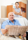 Mature man reading newspaper against sad woman serious men women in home Royalty Free Stock Image