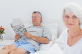 Mature man reading a newspaper in bed men while his wife is sitting on Royalty Free Stock Photo