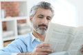 Mature man reading newspaper sitting at home in sofa Stock Photography
