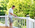 Mature man scraping old paint from outdoor deck Royalty Free Stock Photo