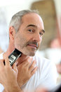 Mature man shaving with razor senior beard electric Royalty Free Stock Photography