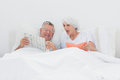 Mature man showing his newspaper to his wife men in bed Royalty Free Stock Photos