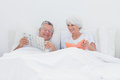 Mature man showing newspaper to his wife men in bed Royalty Free Stock Photography