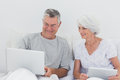 Mature man showing something on his laptop men to wife bed Royalty Free Stock Photo