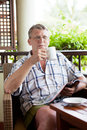 Mature man sits on a balcony Royalty Free Stock Photo
